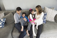Mature couple and two children sitting on living room sofa - ISF15798