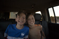 Portrait of brothers smiling in car back seat - ISF15834