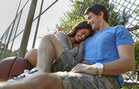 Young couple with basketball sitting by wire fence - ISF15864