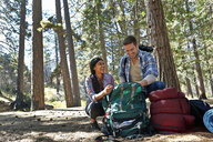 Young couple unpacking camping rucksack in forest, Los Angeles, California, USA - ISF15879
