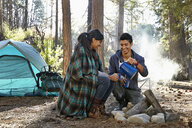 Young couple pouring coffee by campfire in forest, Los Angeles, California, USA - ISF15888