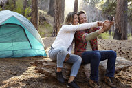 Young camping couple taking smartphone selfie in forest, Los Angeles, California, USA - ISF15894