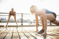 Women stretching on bridge, Montreal, Quebec, Canada - ISF15909