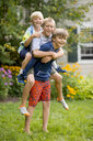 Three boys playing piggyback in garden - ISF16038