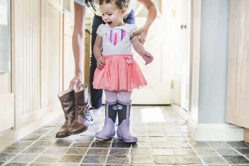 Mother and daughter putting on boots in kitchen - ISF16113