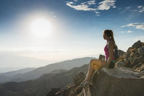 Woman taking break on mountain, Joshua Tree National Park, California, US - ISF16185