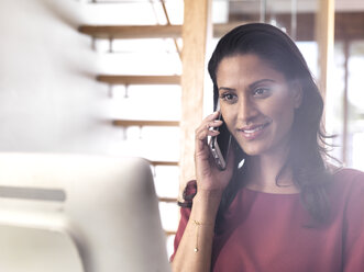 Portrait of smiling businesswoman on the phone in office - ABRF00204