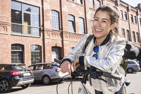 Portrait of laughing young woman leaning on bicycle handlebar - TAMF01099