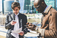 Russia, Moscow, two businessmen using smartphones in the city - WPEF00599