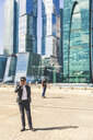 Russia, Moscow, two businessmen using cell phones in the city - WPEF00602