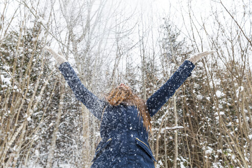 Happy woman throwing with snow and having fun - WPEF00616