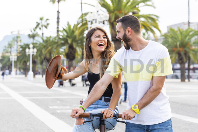 Spain, Barcelona, couple having fun and sharing a ride on a bike together on seaside promenade - WPEF00619