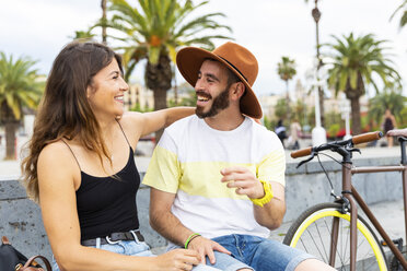 Spain, Barcelona, couple sitting on bench having fun together - WPEF00622