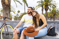 Spain, Barcelona, affectionate couple sitting on bench relaxing - WPEF00625