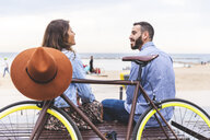 Spain, Barcelona, couple with bicycle sitting at the seaside - WPEF00631