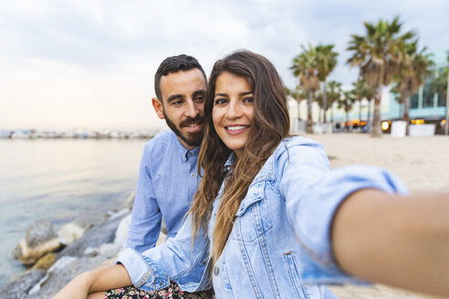 Spain, Barcelona, smiling couple taking a selfie at the seaside - WPEF00634