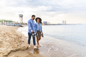 Spain, Barcelona, couple walking barefoot on the beach - WPEF00637