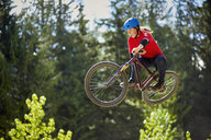 Young female bmx biker jumping mid air in forest - ISF16341