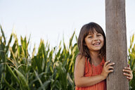 Portrait of girl holding onto field fencepost - ISF16377