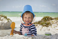 Baby girl with bucket over head on beach, Anna Maria Island, Florida, USA - ISF16408