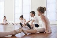 Children sitting on floor practicing ballet position in ballet school - ISF16411