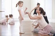 Teacher demonstrating to girl in ballet school - ISF16417