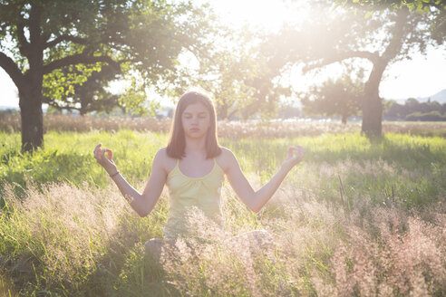 Young girl meditating on meadow at summer evening - LVF07217