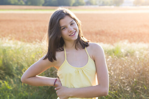 Smiling young girl on meadow at summer evening - LVF07220