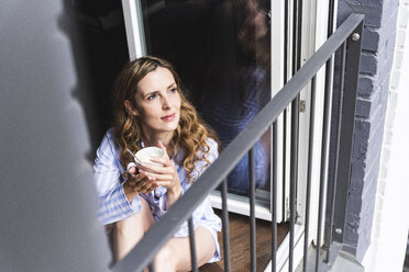Smiling woman in pyjama at home with cup of coffee looking out of balcony door - UUF14325