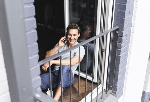 Smiling man in pyjama at home on cell phone at balcony door - UUF14331