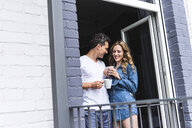 Smiling couple in nightwear at home with cups of coffee at balcony door - UUF14334