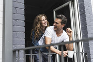 Happy couple in nightwear at home at balcony door - UUF14337