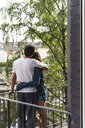Rear view of couple in nightwear standing on balcony hugging - UUF14364