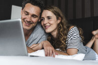Happy couple lying on bed at home looking at laptop - UUF14373