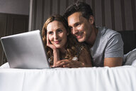 Smiling couple lying on bed at home looking at laptop - UUF14376