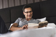 Smiling man lying in bed at home reading a book - UUF14382