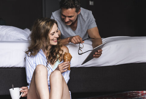 Happy couple in bedroom at home with tablet, coffee and croissant - UUF14388