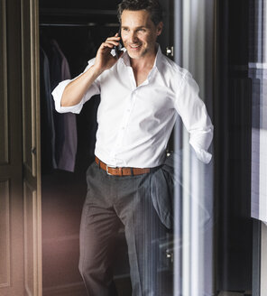 Smiling businessman on cell phone at wardrobe at home - UUF14397