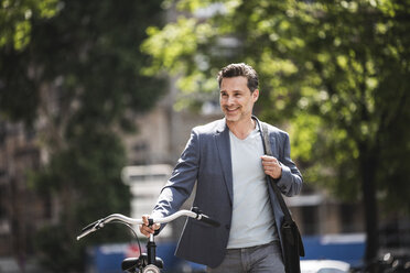 Smiling man pushing bike in the city - UUF14415