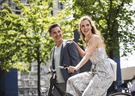 Happy couple with bicycle in the city - UUF14421