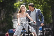 Happy carefree couple with bicycle in the city - UUF14424