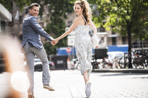 Happy carefree couple running in the city - UUF14427