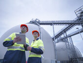 Workers using digital tablet at biomass facility, low angle view - CUF38922