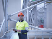 Portrait of worker holding digital tablet at biomass facility - CUF38925