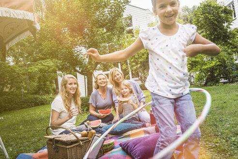 Girl playing with hula hoop at family picnic - CUF39125