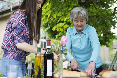Senior woman cutting bread - CUF39140