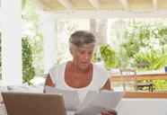 Older woman paying bills on laptop - CUF39180