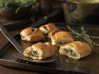 Christmas snack of gourmet sausage rolls and thyme leaves - CUF39342