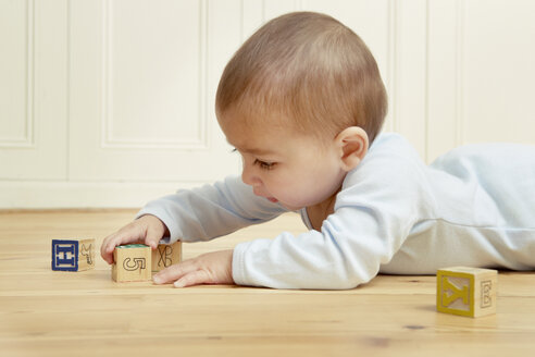 Baby lying on front playing with building blocks - CUF39375