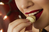 Cropped close up of young woman eating chocolate - CUF39456